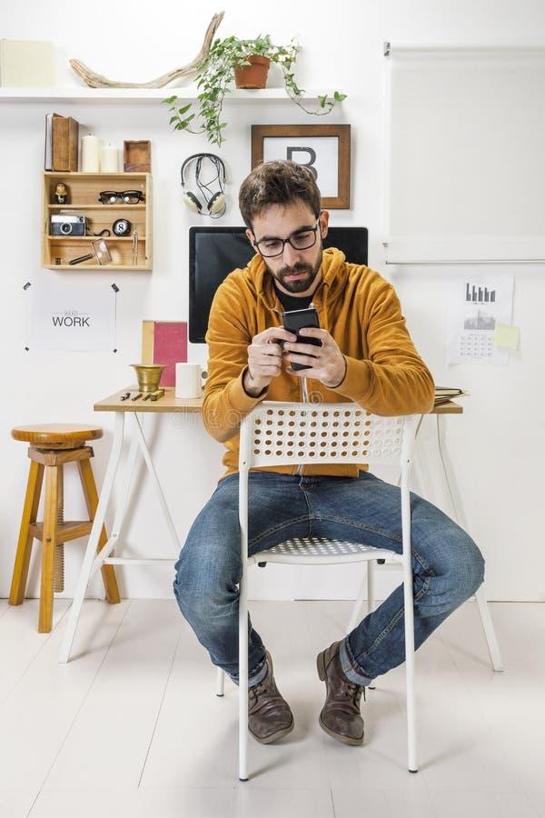 Σύγχρονο δημιουργικό άτομο με το smartphone στο χώρο εργασίας. στοκ φωτογραφία με δικαίωμα ελεύθερης χρήσης