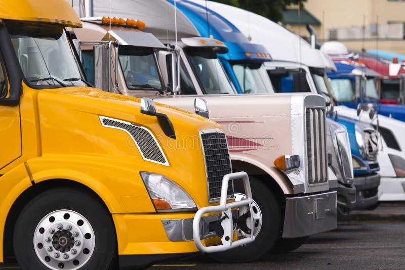 Σύγχρονο κίτρινο ημι φορτηγό στο πρώτο πλάνο άλλων φορτηγών στοκ εικόνα