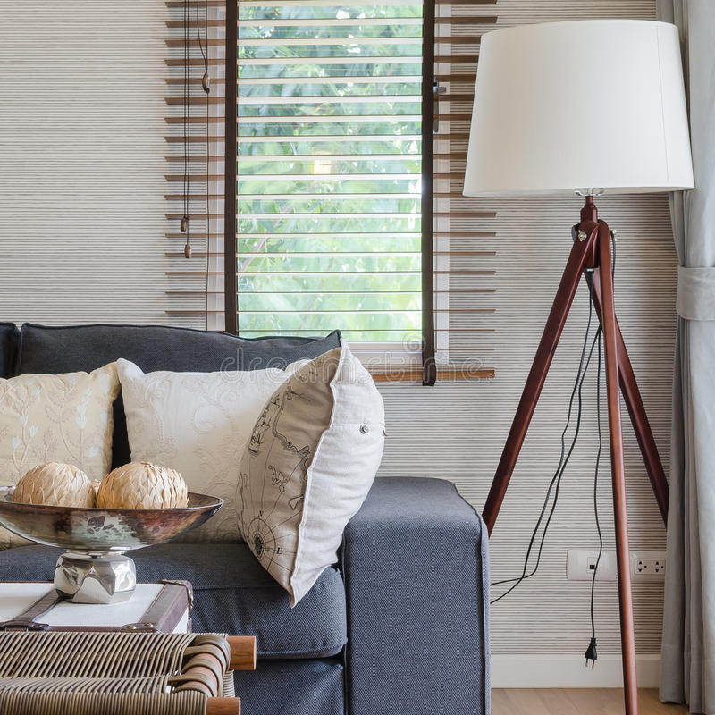 Σύγχρονο καθιστικό με το μαύρο καναπέ και τον ξύλινο λαμπτήρα στοκ εικόνα με δικαίωμα ελεύθερης χρήσης