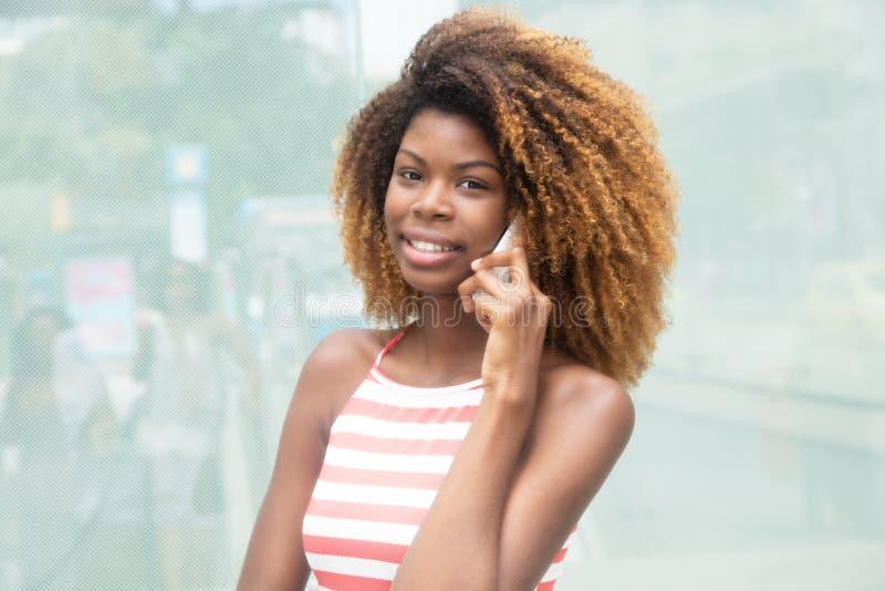 Σύγχρονο κορίτσι αφροαμερικάνων με το τρελλό hairstyle που ακούει στο τηλέφωνο στοκ φωτογραφίες με δικαίωμα ελεύθερης χρήσης