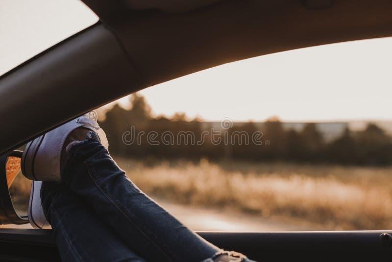 Σύγχρονο κορίτσι hipster που στηρίζεται κατά μια άποψη αυτοκινήτων και θαυμασμού Τεθειμένα ηλιοβασίλεμα πόδια προσοχής οδηγών γυν στοκ φωτογραφία