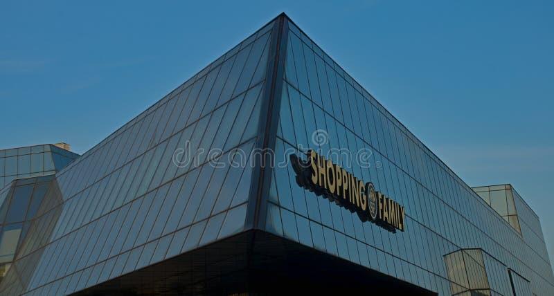 Σύγχρονο κτήριο γυαλιού με το σημάδι με την ψωνίζοντας οικογένεια σημαδιών στοκ φωτογραφία με δικαίωμα ελεύθερης χρήσης