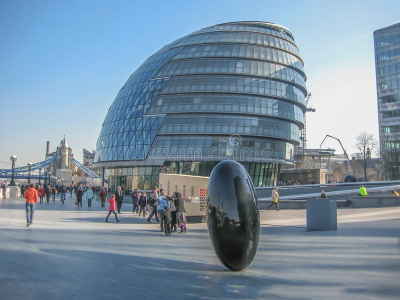 Σύγχρονο κτήριο και ωοειδές γλυπτό, πολλοί άνθρωποι που περπατούν σε μια για τους πεζούς ζώνη στοκ εικόνα