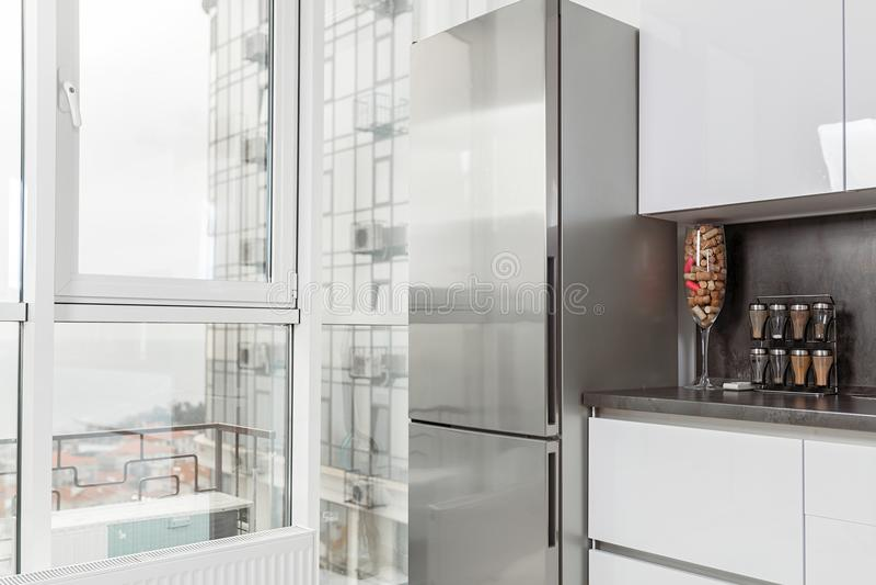 σύγχρονο λευκό κουζινών Στοιχεία κουζινών στο υπόβαθρο ενός μεγάλου πανοραμικού παραθύρου στοκ εικόνες