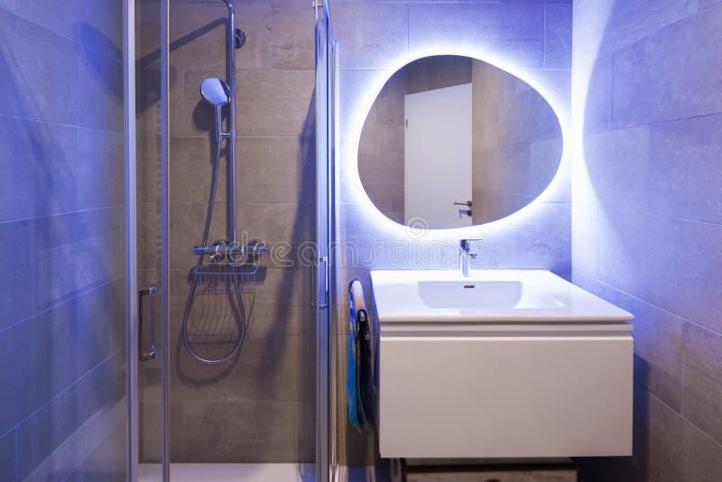 Σύγχρονο μαρμάρινο λουτρό με τον αναδρομικά φωτισμένο καθρέφτη στοκ φωτογραφία με δικαίωμα ελεύθερης χρήσης
