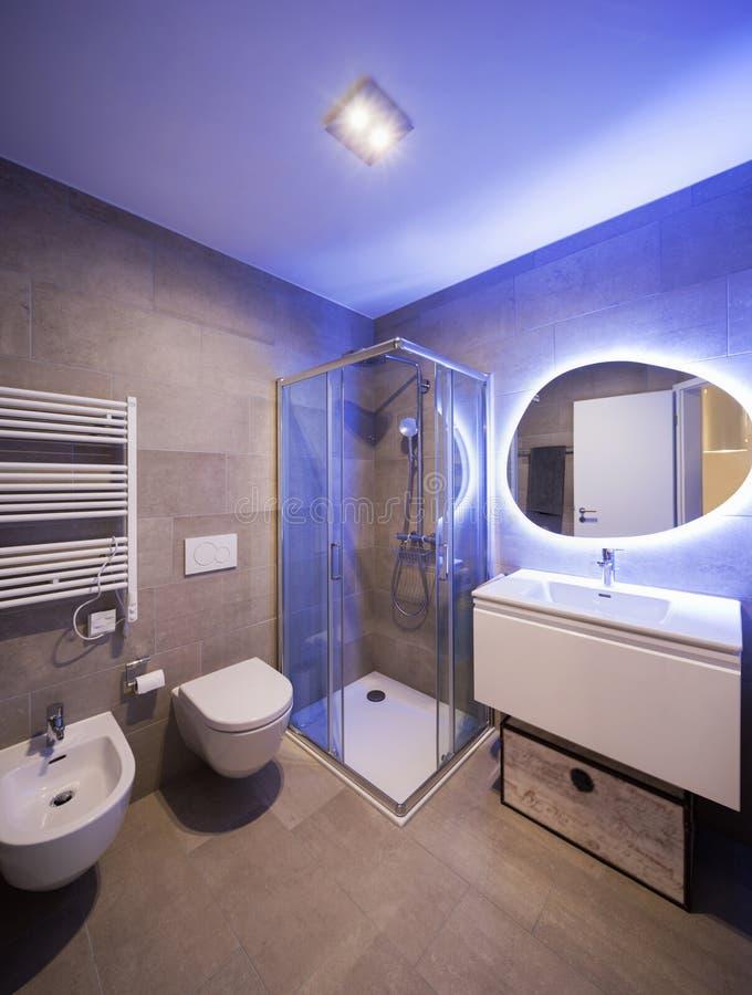 Σύγχρονο μαρμάρινο λουτρό με τον αναδρομικά φωτισμένο καθρέφτη στοκ εικόνες