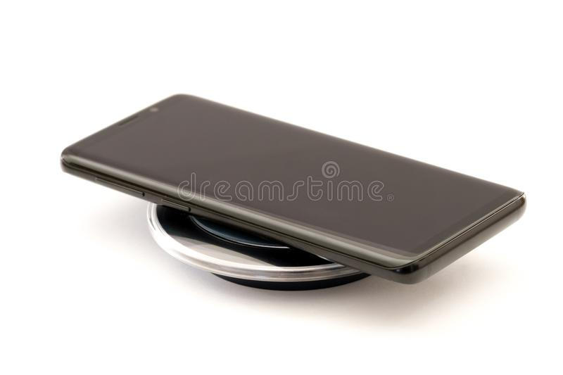 Σύγχρονο μαύρο smartphone που χρεώνει στο ασύρματο μαξιλάρι φορτιστών Απομονωμένος στην άσπρη ανασκόπηση με το ψαλίδισμα του μονο στοκ εικόνα