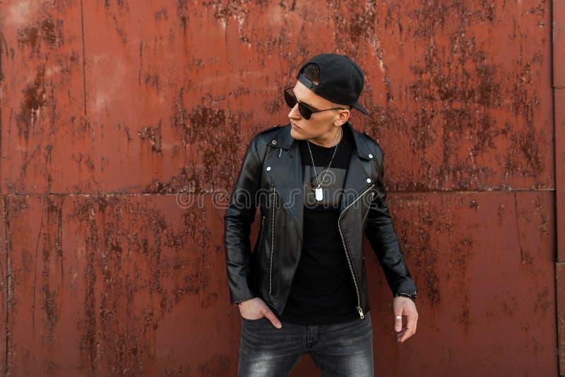 Σύγχρονο μοντέρνο νέο άτομο hipster με τα γυαλιά ηλίου σε ένα μοντέρνο μαύρο σακάκι δέρματος σε μια ΚΑΠ σε μια εκλεκτής ποιότητας στοκ φωτογραφία με δικαίωμα ελεύθερης χρήσης