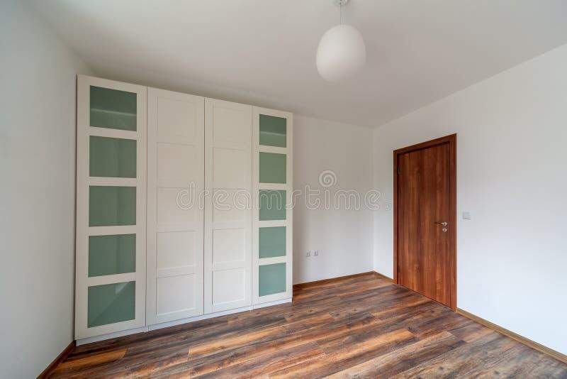 Σύγχρονο σπίτι, κενό δωμάτιο με το άσπρο ντουλάπι ντουλαπών, ξύλινο πάτωμα στοκ φωτογραφίες