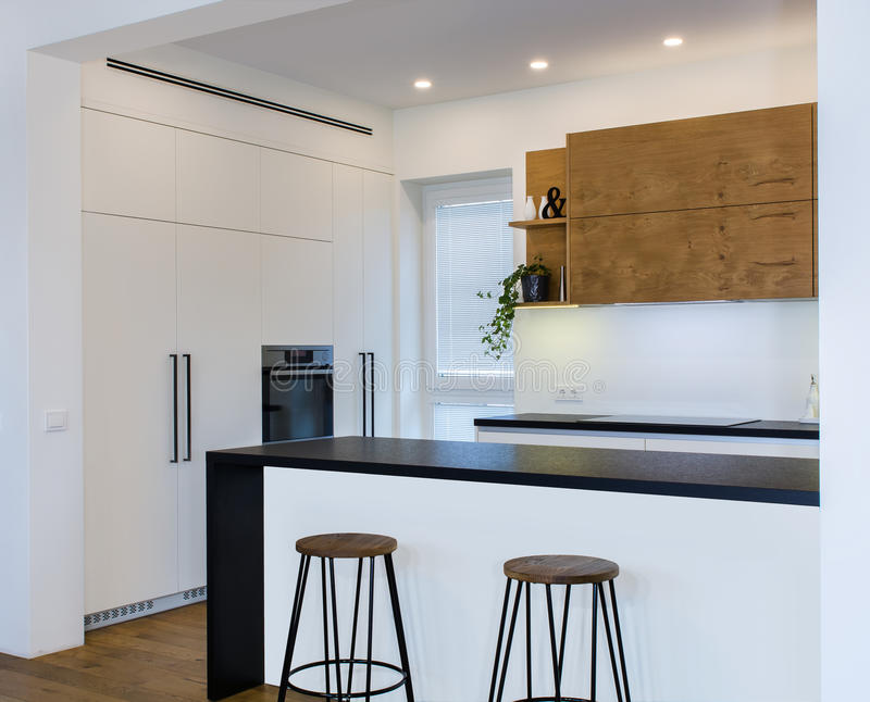 Σύγχρονο σχέδιο κουζινών στο ελαφρύ εσωτερικό με τις ξύλινες εμφάσεις στοκ εικόνα
