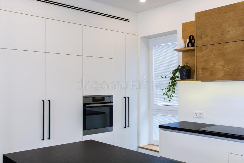 Σύγχρονο σχέδιο κουζινών στο ελαφρύ εσωτερικό με τις ξύλινες εμφάσεις στοκ φωτογραφία