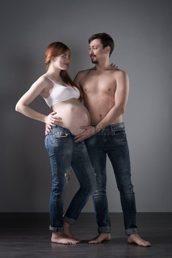 Σύζυγος και έγκυος σύζυγος στο γκρίζο υπόβαθρο στοκ φωτογραφίες