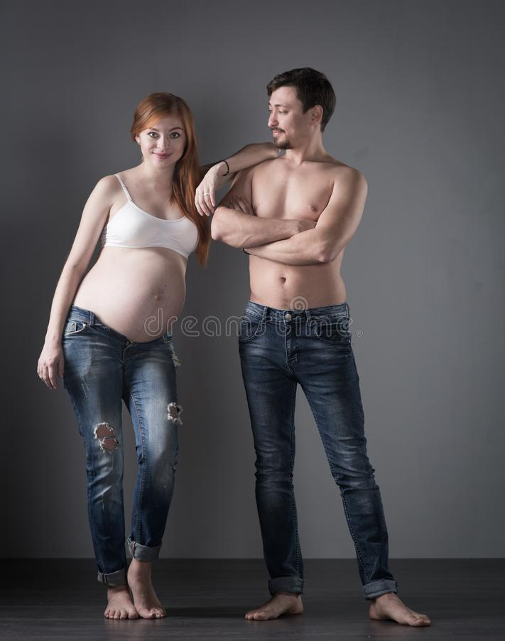 Σύζυγος και έγκυος σύζυγος στο γκρίζο υπόβαθρο στοκ εικόνα