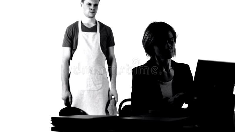 0 σύζυγος με το τηγάνι που εξετάζει την εργαζόμενη επιχειρησιακή σύζυγο, κούραση μικροδουλειών σπιτιών στοκ εικόνες