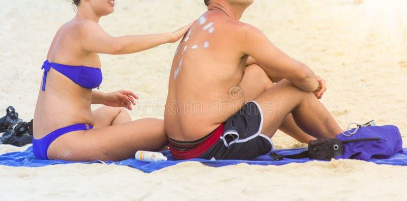 Σύζυγος που εφαρμόζει sunscreen το λοσιόν στο σύζυγό της πίσω στην παραλία στοκ εικόνες