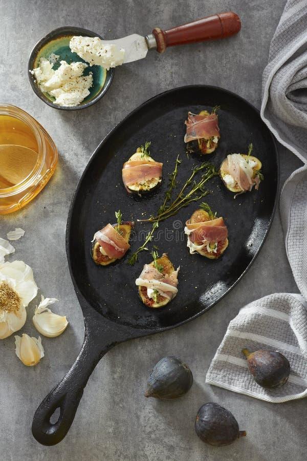 Σύκα και τυρί που τυλίγονται στο κρέας σε ένα τηγάνι χυτοσιδήρου στοκ εικόνα με δικαίωμα ελεύθερης χρήσης