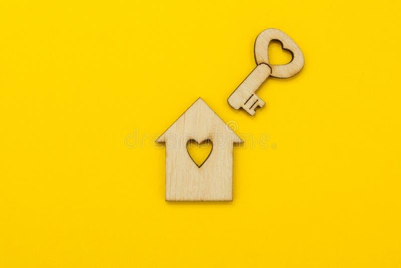 Σύμβολο ενός μικρού σπιτιού και ένα κλειδί με μια καρδιά σε ένα κίτρινο υπόβαθρο στοκ φωτογραφία
