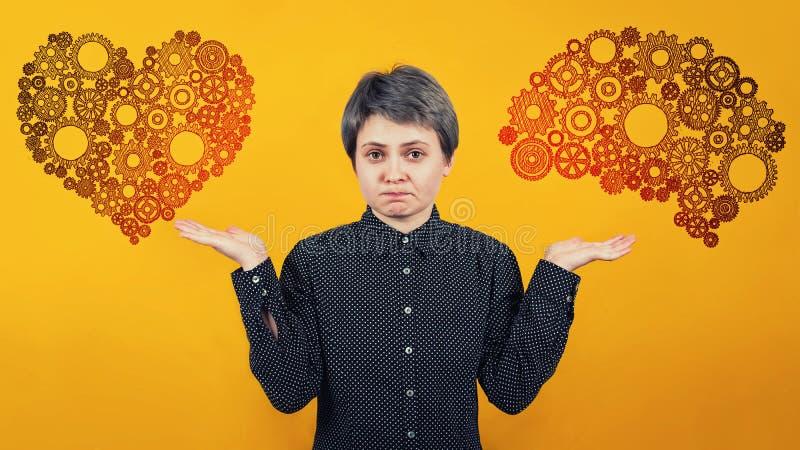Σύμβολο καρδιών και εγκεφάλου στις διαφορετικές πλευρές πέρα από τον κίτρινο τοίχο Δύσκολη απόφαση, επιλογή μεταξύ της καρδιάς κα στοκ φωτογραφία