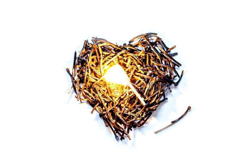 Σύμβολο καρδιών φιαγμένο από καίω-κάτω κινηματογράφηση σε πρώτο πλάνο αντιστοιχιών με μια καίγοντας αντιστοιχία στο κέντρο, που α στοκ εικόνα
