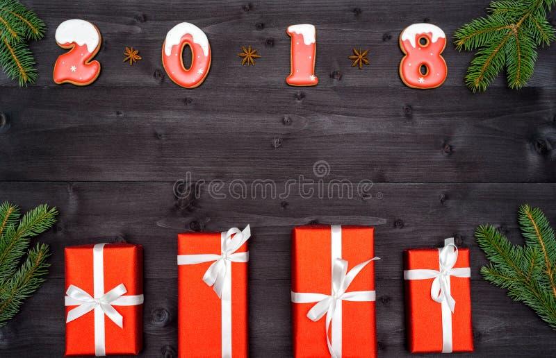 Σύμβολο σημαδιών καλής χρονιάς 2018 από τα κόκκινα και άσπρα μπισκότα μελοψωμάτων στο σκοτεινό ξύλινο υπόβαθρο με τα κόκκινα κιβώ στοκ φωτογραφία με δικαίωμα ελεύθερης χρήσης