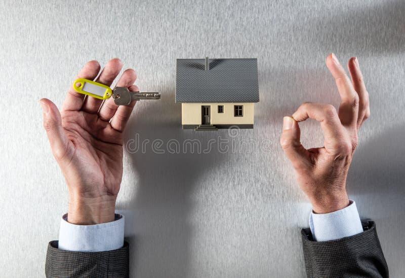 Σύμβολο της εγχώριας ιδιοκτησίας zen με το κλειδί σπιτιών στα χέρια στοκ φωτογραφίες