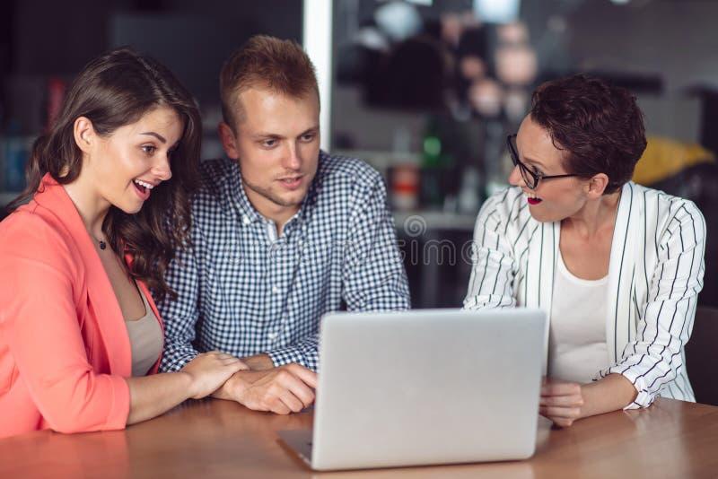 Σύμβουλος επενδύσεων που κάνει μια παρουσίαση σε ένα φιλικό χαμογελώντας νέο ζεύγος που κάθεται στο γραφείο της στο γραφείο στοκ φωτογραφίες με δικαίωμα ελεύθερης χρήσης
