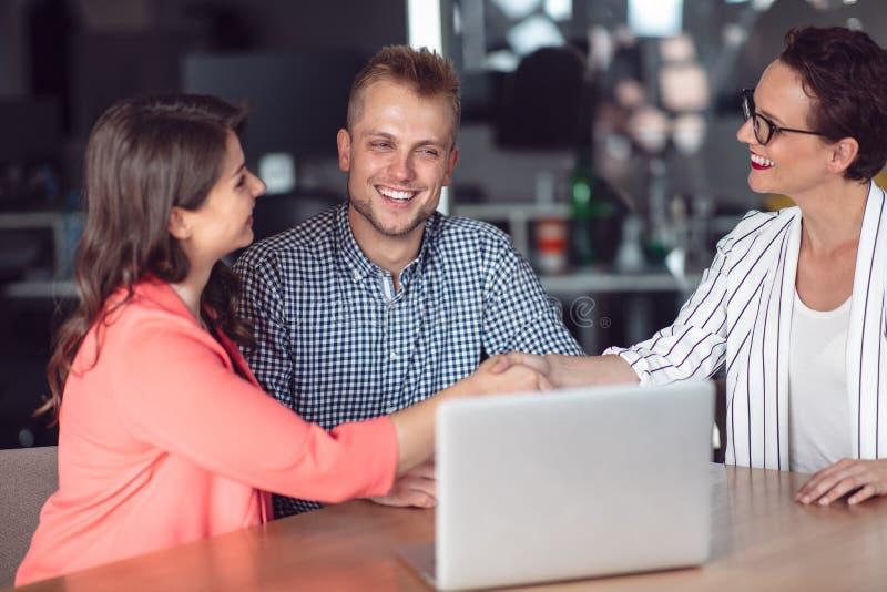 Σύμβουλος επενδύσεων που κάνει μια παρουσίαση σε ένα φιλικό χαμογελώντας νέο ζεύγος που κάθεται στο γραφείο της στο γραφείο στοκ φωτογραφία με δικαίωμα ελεύθερης χρήσης