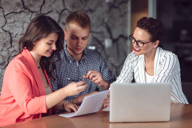 Σύμβουλος επενδύσεων που κάνει μια παρουσίαση σε ένα φιλικό χαμογελώντας νέο ζεύγος που κάθεται στο γραφείο της στο γραφείο στοκ εικόνες