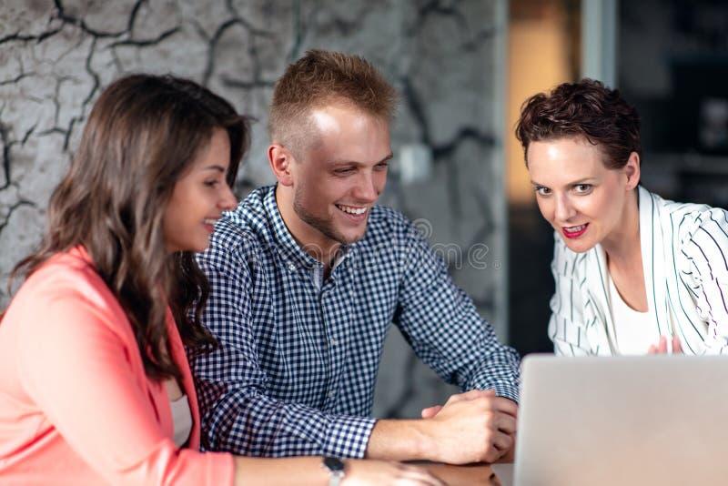 Σύμβουλος επενδύσεων που κάνει μια παρουσίαση σε ένα φιλικό χαμογελώντας νέο ζεύγος που κάθεται στο γραφείο της στο γραφείο στοκ φωτογραφία