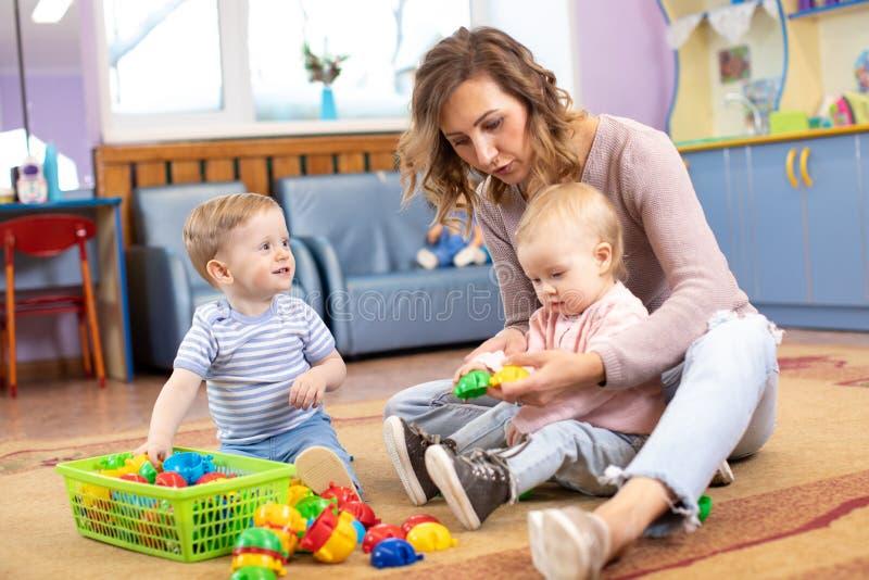 Σύμβουλος και χρονών μωρά 1 που παίζουν με τα εκπαιδευτικά παιχνίδια στον παιδικό σταθμό στοκ φωτογραφία με δικαίωμα ελεύθερης χρήσης
