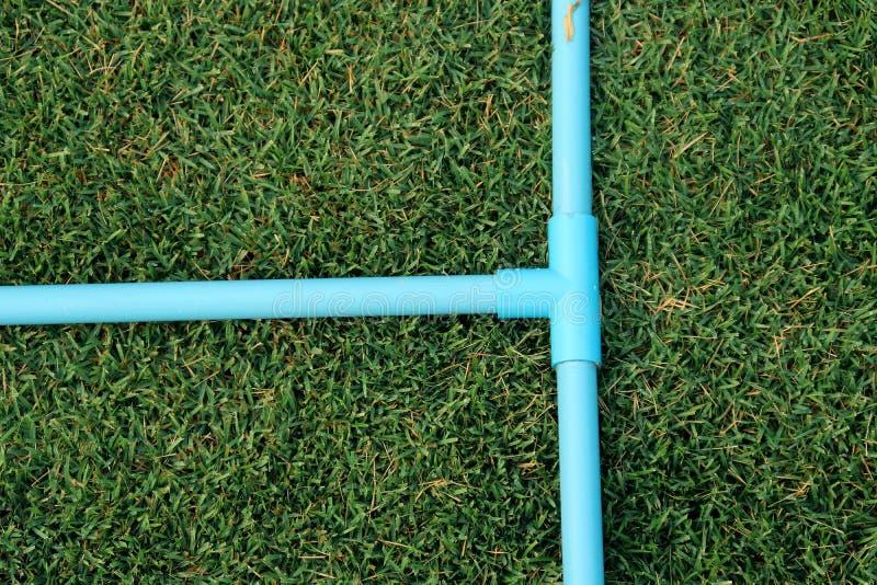 Σύνδεση σωλήνων, σωλήνας PVC υποδοχών Τ, μπλε σωλήνας PVC τρόπων δέντρων στον πράσινο κήπο στοκ φωτογραφία