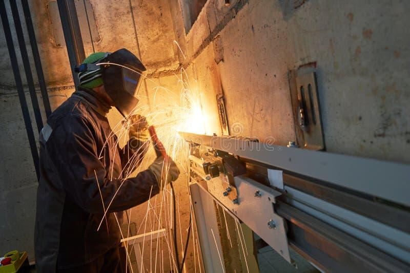 Σύνδεσμοι ανελκυστήρων συγκόλλησης εργαζομένων ανελκυστήρων στον άξονα ανελκυστήρων στοκ φωτογραφία με δικαίωμα ελεύθερης χρήσης