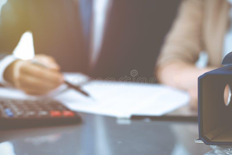 Σύνδεσμοι με τα έγγραφα που περιμένουν να υποβληθεί σε επεξεργασία με τον επιχειρηματία ή το λογιστή πίσω στη θαμπάδα Λογιστικός  στοκ εικόνες με δικαίωμα ελεύθερης χρήσης