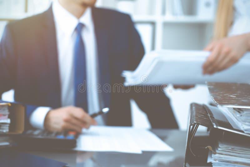 Σύνδεσμοι με τα έγγραφα που περιμένουν να υποβληθεί σε επεξεργασία με τον επιχειρηματία ή το λογιστή πίσω στη θαμπάδα Λογιστικός  στοκ φωτογραφίες με δικαίωμα ελεύθερης χρήσης