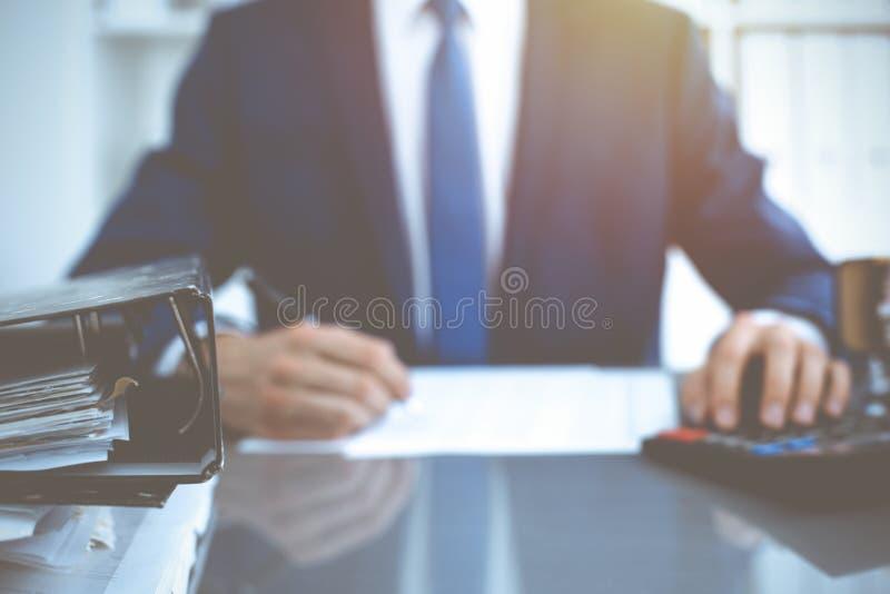 Σύνδεσμοι με τα έγγραφα που περιμένουν να υποβληθεί σε επεξεργασία με τον επιχειρηματία ή το λογιστή πίσω στη θαμπάδα Λογιστικός  στοκ εικόνα με δικαίωμα ελεύθερης χρήσης
