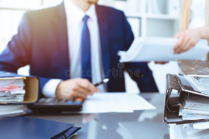 Σύνδεσμοι με τα έγγραφα που περιμένουν να υποβληθεί σε επεξεργασία με τον επιχειρηματία ή το λογιστή πίσω στη θαμπάδα Λογιστικός  στοκ φωτογραφία