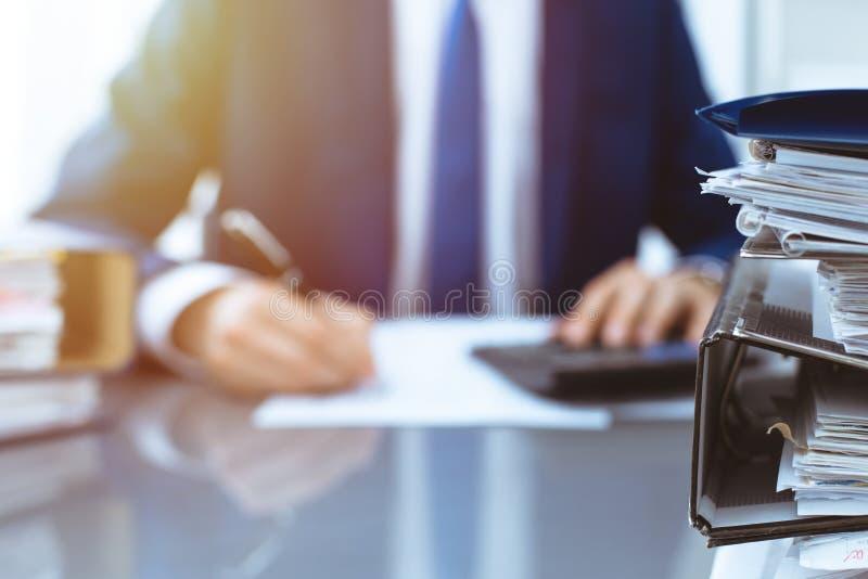 Σύνδεσμοι με τα έγγραφα που περιμένουν να υποβληθεί σε επεξεργασία με τον επιχειρηματία ή το λογιστή πίσω στη θαμπάδα Λογιστικός  στοκ φωτογραφία με δικαίωμα ελεύθερης χρήσης
