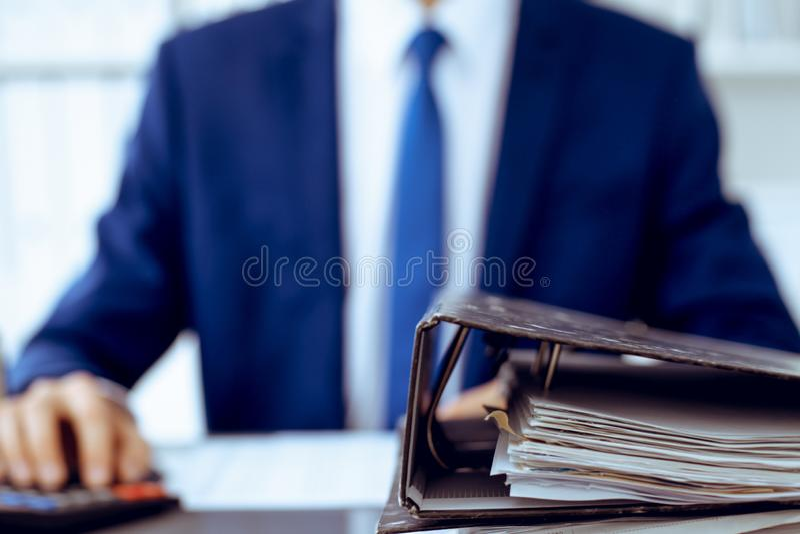 Σύνδεσμοι με τα έγγραφα που περιμένουν να υποβληθεί σε επεξεργασία με τον επιχειρηματία ή το λογιστή πίσω στη θαμπάδα Λογιστικός  στοκ εικόνα