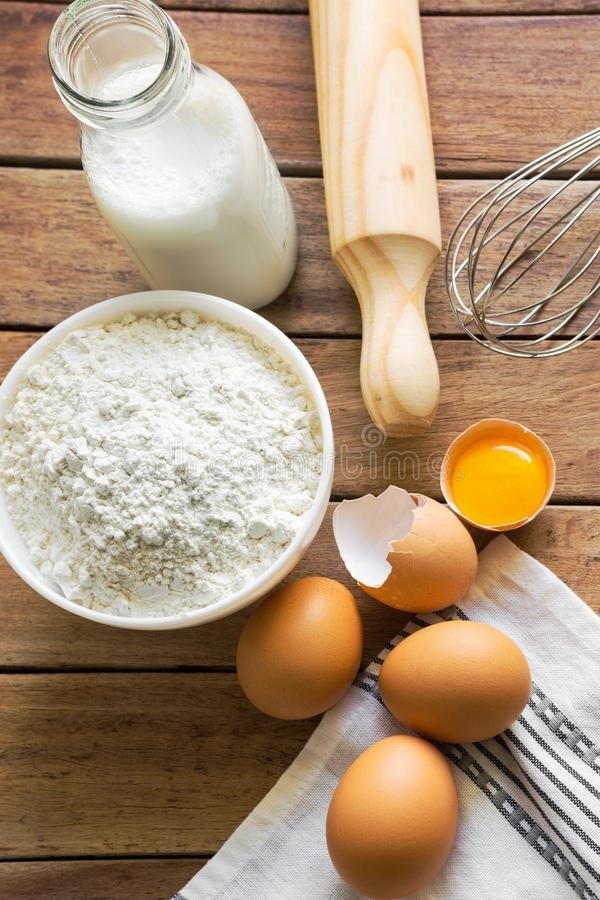 Σύνθεση από τα συστατικά ψησίματος Ραγισμένος αυγά φωτεινός κίτρινος λέκιθος κοχυλιών Γάλα στο αλεύρι μπουκαλιών γυαλιού που τακτ στοκ φωτογραφία με δικαίωμα ελεύθερης χρήσης