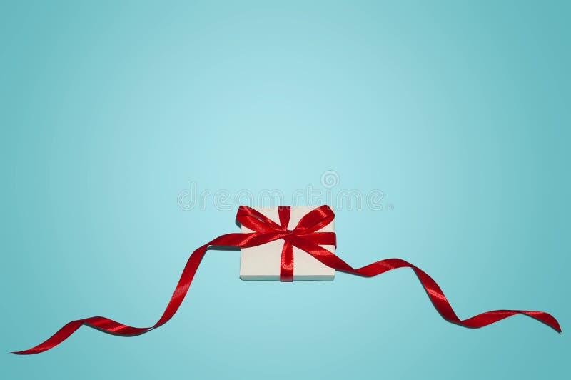 Σύνθεση διακοπών Χριστουγέννων Το νέο δώρο έτους στο άσπρο κιβώτιο με την κόκκινη κορδέλλα στο μπλε επίπεδο υποβάθρου βάζει τη το στοκ εικόνα με δικαίωμα ελεύθερης χρήσης