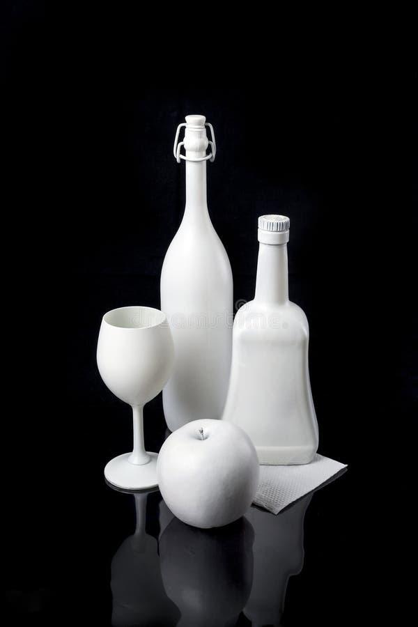 Σύνθεση: δύο μπουκάλια, ένα γυαλί και ένα μήλο είναι στο άσπρο χρώμα σε ένα μαύρο υπόβαθρο στοκ φωτογραφίες