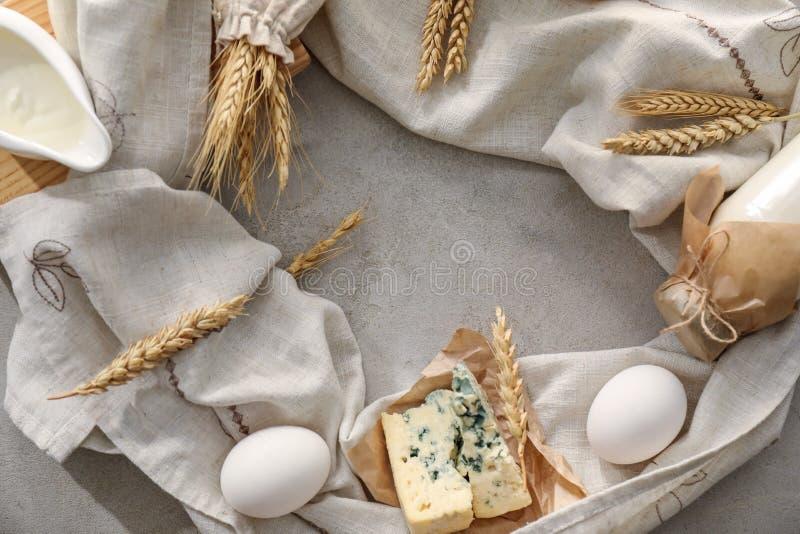 Σύνθεση με τα διαφορετικά γαλακτοκομικά προϊόντα και spikelets στο γκρίζο υπόβαθρο στοκ εικόνα