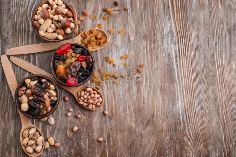 Σύνθεση με τα διαφορετικά είδη καρυδιών, ξηρών καρπών και μούρων στο ξύλινο υπόβαθρο στοκ φωτογραφία