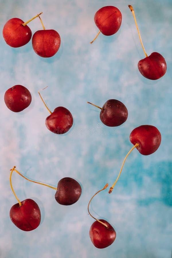 Σύνθεση με τα πετώντας γλυκά κόκκινα μούρα για το μετεωρισμό στο μπλε υπόβαθρο Τρόφιμα Levitating, μούρα Levitating στοκ εικόνα με δικαίωμα ελεύθερης χρήσης