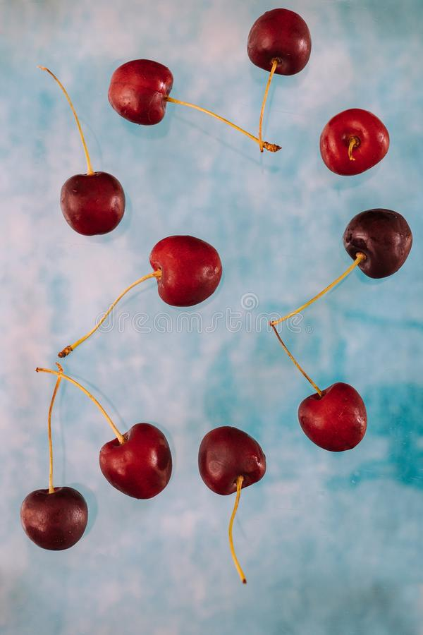 Σύνθεση με τα πετώντας γλυκά κόκκινα μούρα για το μετεωρισμό στο μπλε υπόβαθρο Τρόφιμα Levitating, μούρα Levitating στοκ εικόνα