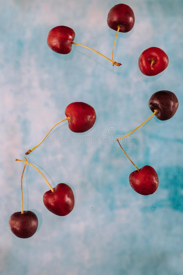 Σύνθεση με τα πετώντας γλυκά κόκκινα μούρα για το μετεωρισμό στο μπλε υπόβαθρο Τρόφιμα Levitating, μούρα Levitating στοκ εικόνες με δικαίωμα ελεύθερης χρήσης