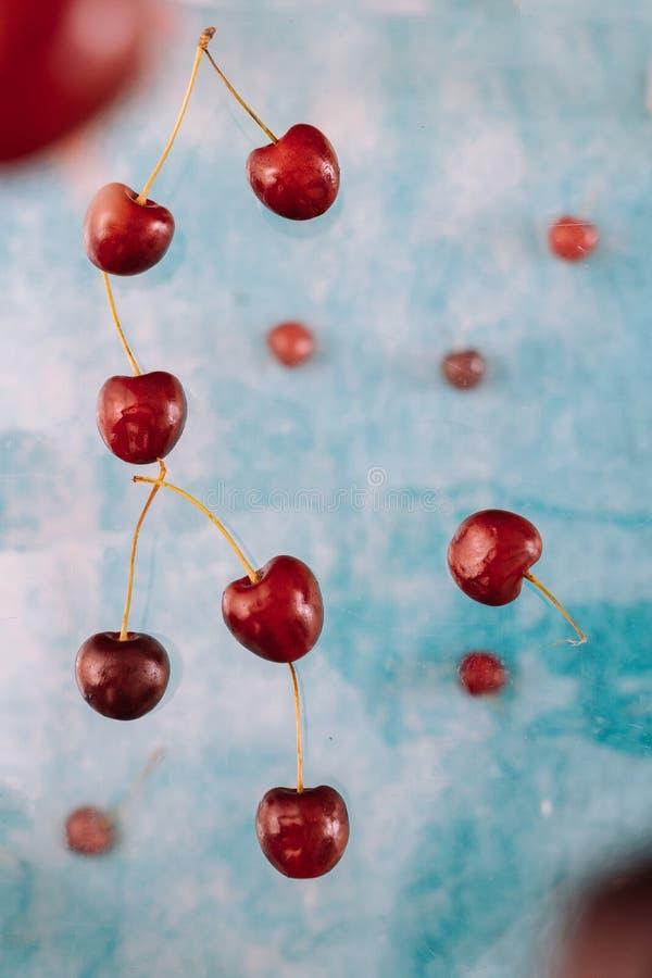 Σύνθεση με τα πετώντας γλυκά κόκκινα μούρα για το μετεωρισμό στο μπλε υπόβαθρο Τρόφιμα Levitating, μούρα Levitating στοκ εικόνες