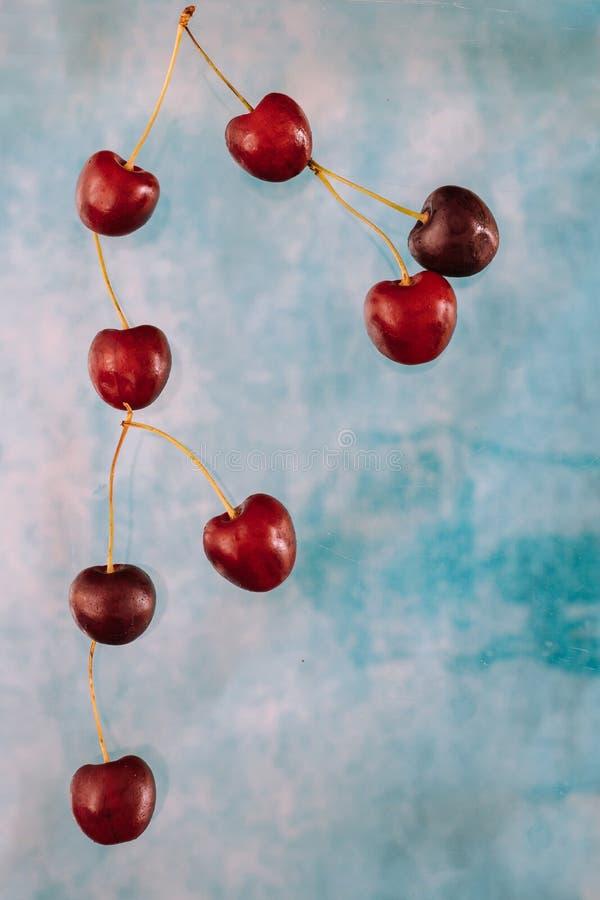 Σύνθεση με τα πετώντας γλυκά κόκκινα μούρα για το μετεωρισμό στο μπλε υπόβαθρο Τρόφιμα Levitating, μούρα Levitating στοκ φωτογραφία