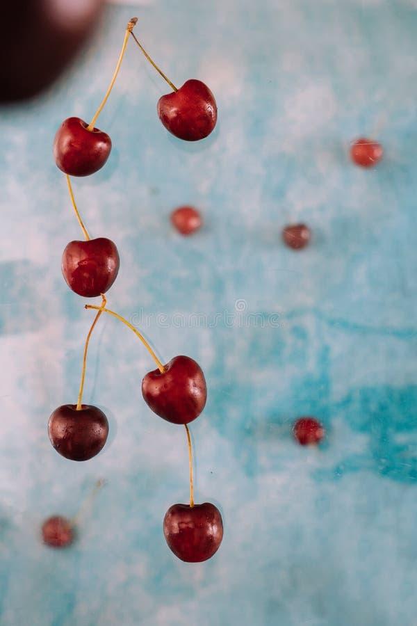 Σύνθεση με τα πετώντας γλυκά κόκκινα μούρα για το μετεωρισμό στο μπλε υπόβαθρο Τρόφιμα Levitating, μούρα Levitating στοκ φωτογραφίες