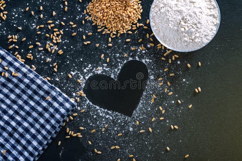 Σύνθεση με τα σιτάρια σίτου, αλεύρι με τη μορφή καρδιών στο μαύρο υπόβαθρο στοκ φωτογραφία με δικαίωμα ελεύθερης χρήσης
